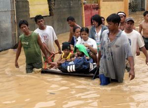 Residents of Manila, Philippines use a raft to rescue children from floods. Photo By JASON GUITERREZ/IRIN