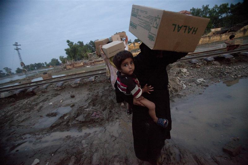 """A survivor of the floods in Pakistan carries relief supplies. UN Secretary General Ban Ki-Moon said, """"In the past I have visited scenes of many natural disasters around the world, but nothing like this. The scale of this disaster is so large, so many people, in so many places, in so much need. """""""