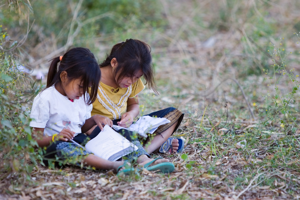 Girls reading in their schoolyard in Laos. PHOTO: London Public Library