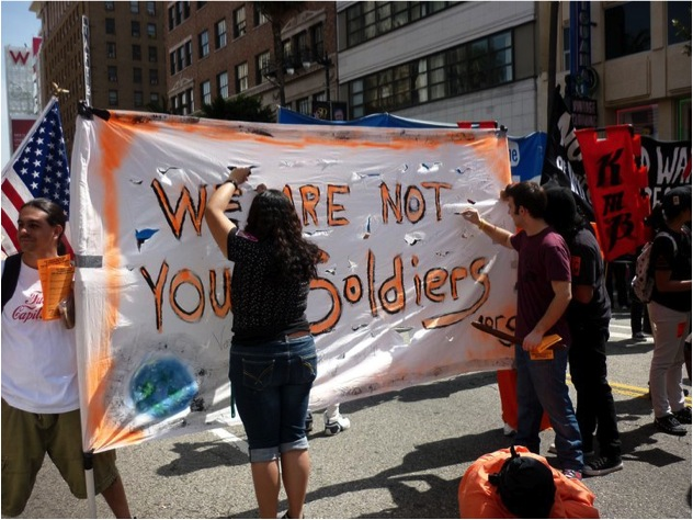 Young people involved with the We Are Not Your Soldiers anti-recruitment campaign prepare a protest banner in New York City. PHOTO: Debra Sweet/Flickr
